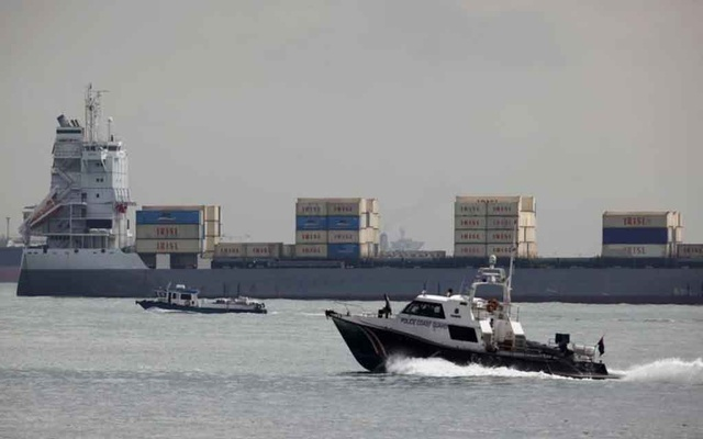 A police coast guard vessel patrols past container ship Valili carrying Islamic Republic of Iran Shipping Lines (IRISL) cargo in the waters of Singapore Strait off Sentosa island February 6, 2012. REUTERS/Edgar Su
