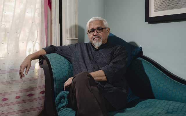 """Author Amitav Ghosh at his home in Brooklyn, Aug 22, 2019. His 12th book, """"Gun Island,"""" is about a rare book dealer drawn into a globe-spanning adventure with Bangladeshi migrants in Libya, dolphins in the Mediterranean and venomous water snakes in California. The New York Times"""
