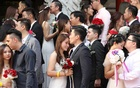 Newlywed couples kiss during a mass wedding in Kuala Lumpur, Malaysia, Sep 9, 2019. A mass wedding ceremony was held for 99 couples on the ninth day of the ninth month, considered an auspicious date, at a Chinese temple in the city. REUTERS