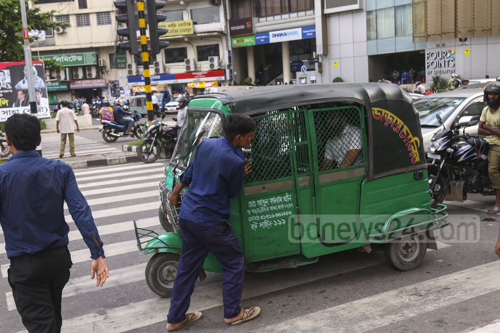 An autorickshaw driver pushing the vehicle backwards from the zebra crossing after watching himself being photographed at Gulshan-2 in Dhaka on Wednesday. Photo: Mahmud Zaman Ovi