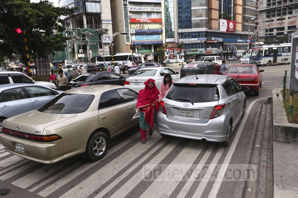 Pedestrians zigzagging through cars stopped on the zebra crossing at Gulshan-2 in Dhakaon Wednesday. Photo: Mahmud Zaman Ovi