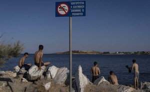 Migrants from Afghanistan cool off next to a sign that says