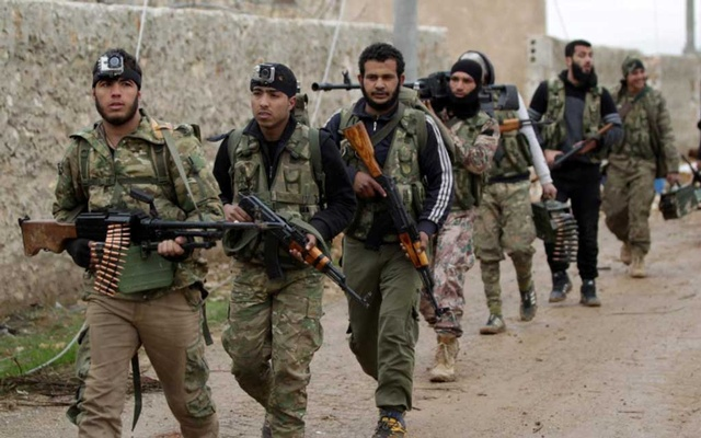 Rebel fighters walk carrying their weapons on the outskirts of the northern Syrian town of al-Bab, Syria Jan 15, 2017. REUTERS