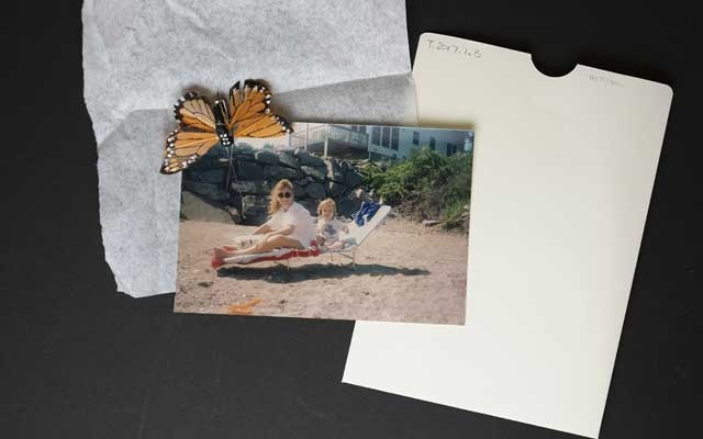 A photo of Candace Lee Williams with her little brother Corey, and attached monarch butterfly pin, at the 9/11 Memorial Museum in New York, Sept 3, 2019. Items left at the plaza of the museum have made their way into its vast storage facilities, and are considered valuable expressions of mourning that continue the narrative of Sept 11. (Caitlin Ochs/The New York Times)