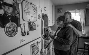A photo by Mary F Calvert shows Katie Hanson being hugged by her husband, Ethan, in the kitchen of their home in Austin, Minn, Apr 24, 2018. Ethan Hanson was one of a group of Marine recruits who were sexually assaulted in the showers during boot camp at Camp Pendleton, Calif. Like many of the sexual assaults on servicemen, it was a hazing exercise, meant to humiliate and intimidate young troops. The New York Times