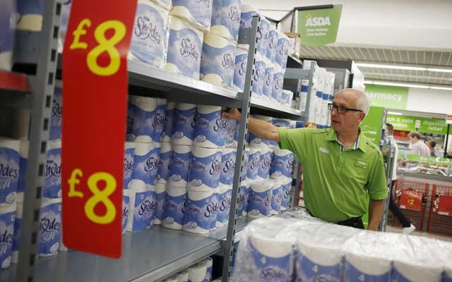 FILE PHOTO: An employee stocks toilet paper along an aisle of an Asda store in Kendal, northwest England, Britain August 30, 2015. Reuters