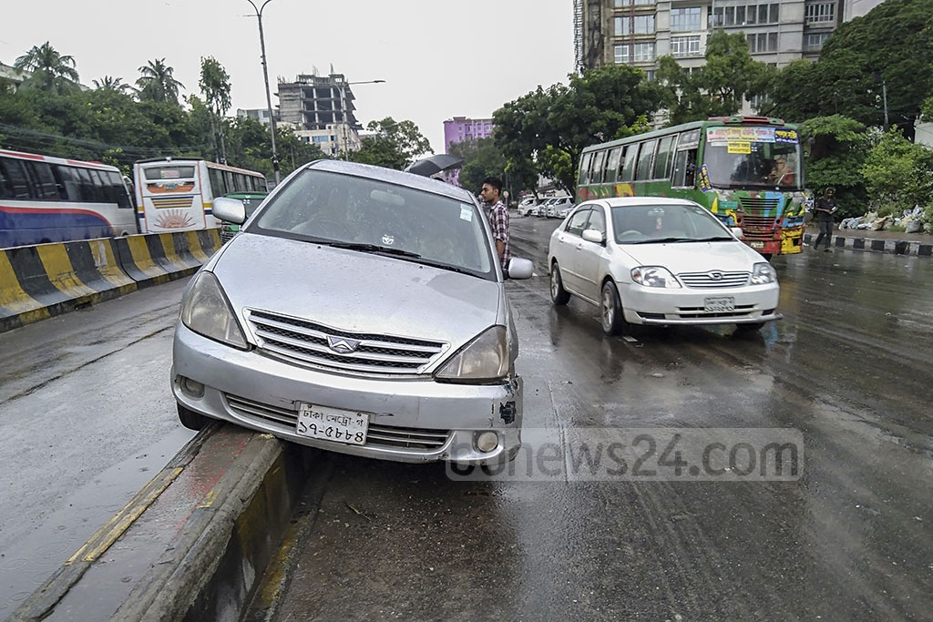 A car veered onto the road-divider at Paltan intersection in Dhaka on Friday morning amid sporadic rains.