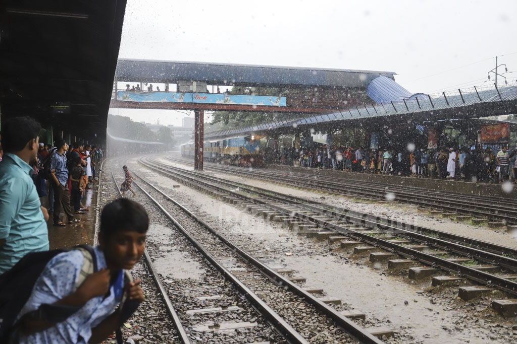 Passengers waiting for trains on a platform of Airport Railway Station in Dhaka amid rain on Friday. Photo: Asif Mahmud Ove