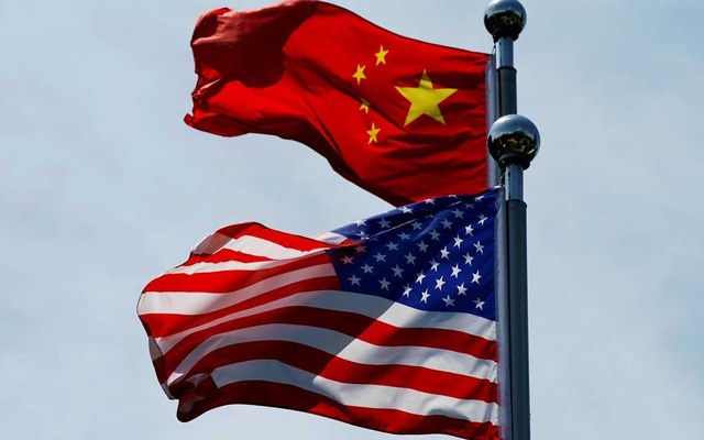 FILE PHOTO: Chinese and US flags flutter near The Bund, before U.S. trade delegation meet their Chinese counterparts for talks in Shanghai, China July 30, 2019. Reuters