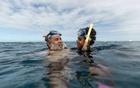 Murrumu of Walubara, left, snorkels with his son, Thoyo of Walubara, at the Great Barrier Reef in Australia on Aug 8, 2019. He says the Great Barrier Reef is part of the Yidinji Territory, not Australia. The New York Times