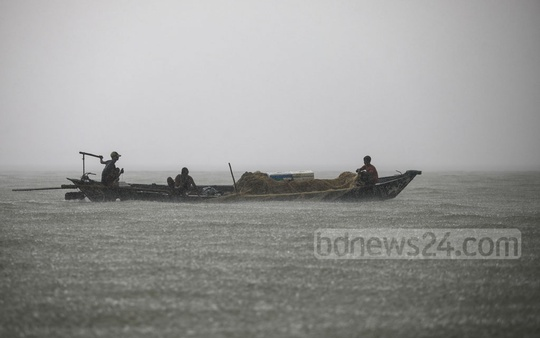 Fishermen are drenched in rain as they catch fishes in the Meghna River. This photo was clicked in Munshiganj's Gazaria. Photo: Mostafigur Rahman