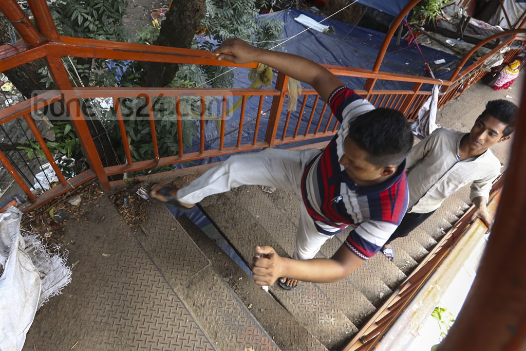 Pedestrians crossing a stair with its broken strip hanging from the staircase of a footbridge near the flower market at Sahbagh in Dhaka. Photo: Mahmud Zaman Ovi
