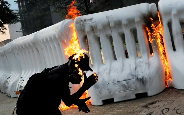 An anti-government protester catches fire after throwing Molotov cocktail during a demonstration near Central Government Complex in Hong Kong, China, September 15, 2019. Reuters
