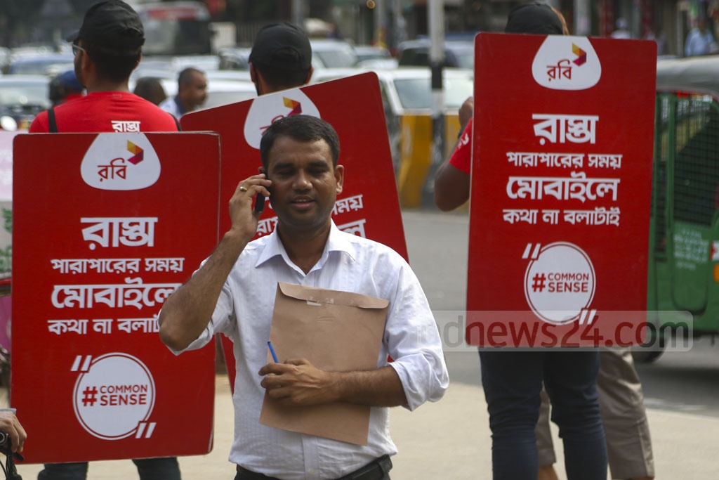 Robi stages an awareness campaign at Gulshan-1 intersection in Dhaka against the use of mobile phones while crossing the street. But a man engrossed in a telephone conversation nonchalantly walks past the campaign messages. Photo: Mahmud Zaman Ovi
