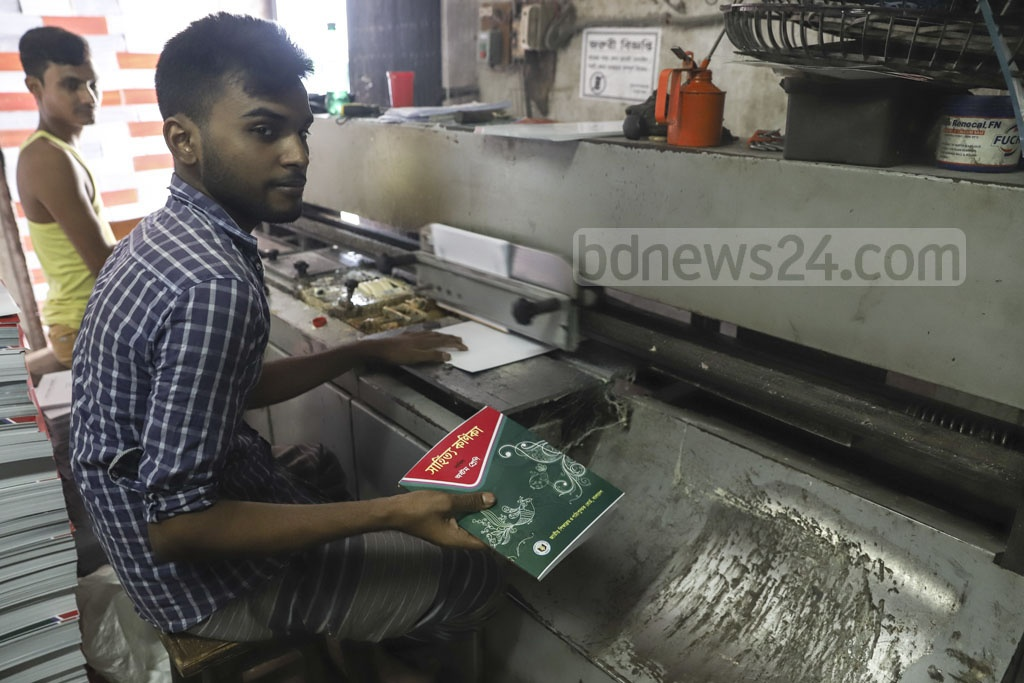 A printing worker lays covers on the textbooks using a machine at Sutrapur in Old Dhaka. Photo: Abdullah Al Momin