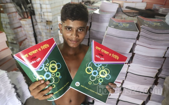 A worker displays textbooks at a printing press at Sutrapur in Old Dhaka. Photo: Abdullah Al Momin