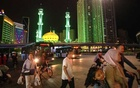 Pedestrians near a mosque with its Arabic style minarets and dome brightly lit at night, in Linxia, China, Sept 14, 2019. The New York Times.