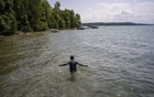Hefzur Rahman, a Rohingya refugee who fled the genocide in Myanmar, wades to shore after tubing in Elk Lake in Elk Rapids, Mich., Aug. 3, 2019. Thousands of Rohingya have quietly settled in the United States, but for children who fled violence in Myanmar, bringing their parents to join them is becoming a distant hope. (Todd Heisler/The New York Times)