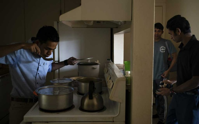 Rohim Mohammod, left, prepares a meal while visiting other Rohingya refugees living in Grand Rapids, Mich., Aug. 4, 2019. Thousands of Rohingya have quietly settled in the United States, but for children who fled violence in Myanmar, bringing their parents to join them is becoming a distant hope. (Todd Heisler/The New York Times)