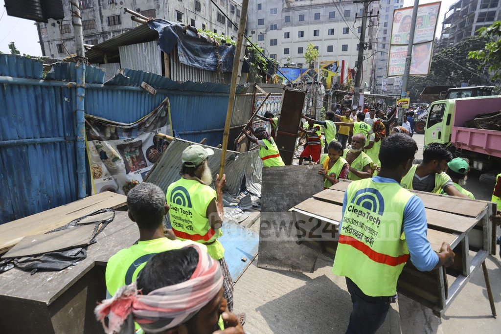 Dhaka North City Corporation workers bulldozing illegal structures on the footpaths at Sector-3 in Uttara on Sunday. Photo: Asif Mahmud Ove