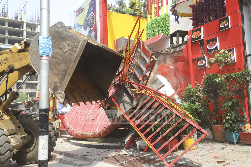Dhaka North City Corporation workers bulldozing an entrance and staircases built illegally on the sidewalks at Section-3 in Uttara on Sunday. Photo: Asif Mahmud Ove