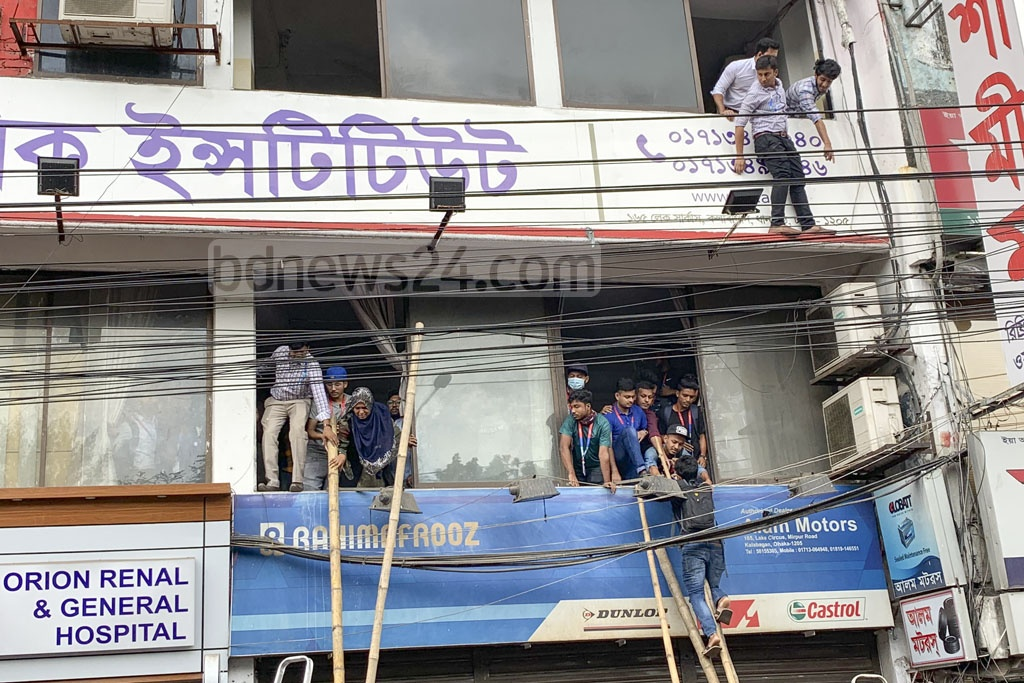 Students using bamboos to climb down from the first and second floors of the Daffodil University in Dhaka's Kalabagan after a fire was reported on Tuesday.