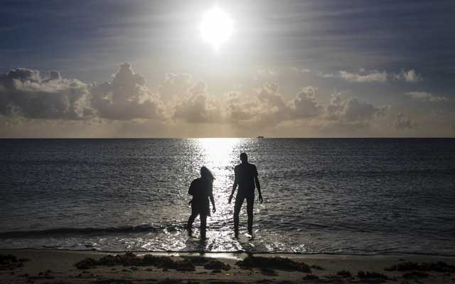 FILE-- People wade into the Atlantic Ocean in Miami Beach, Fla., Sept. 1, 2019. Earth's oceans are under severe strain from climate change, a major new United Nations report issued on Sept. 25 warns, threatening everything from the ability to harvest seafood to the well-being of hundreds of millions of people living along the coasts. (Scott McIntyre/The New York Times)