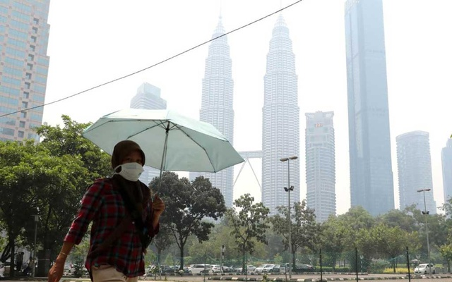 FILE PHOTO: A woman wears a mask as Petronas Twin Tower is shrouded in haze in Kuala Lumpur, Malaysia, Sep 11, 2019. REUTERS