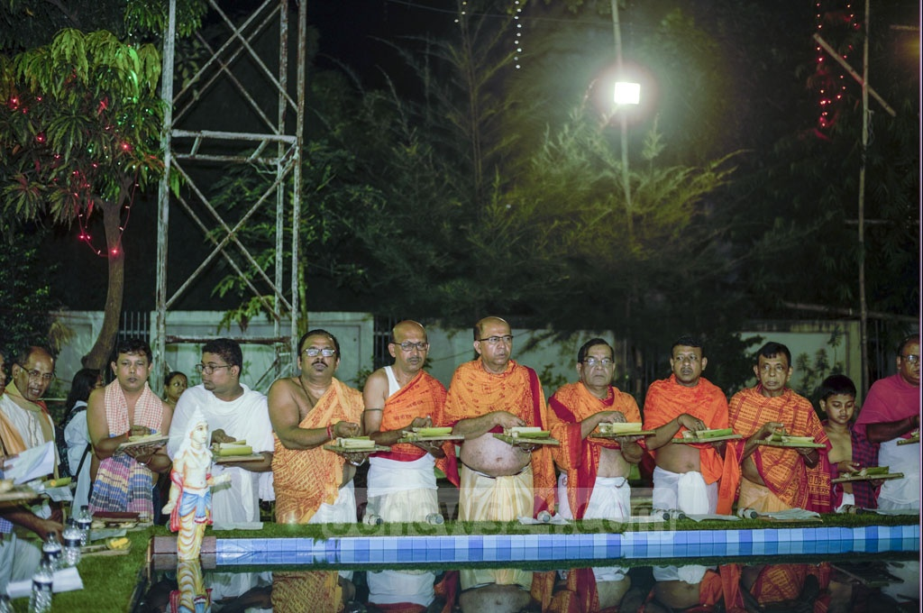 The festivities of Durga Puja begin with religious psalms by the side of a waterbody, at Khamarbari Puja Mandap in Dhaka on Saturday.
