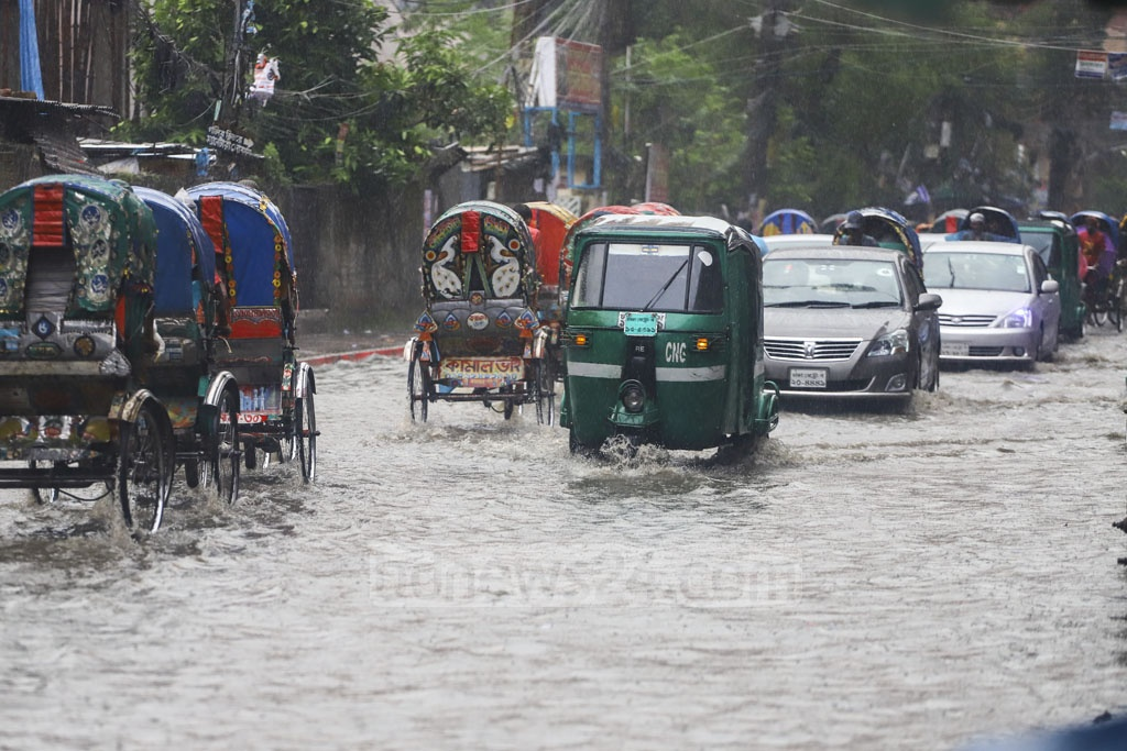 Vehicles wade through logged rain water in Dhaka's Jigatala on Sunday. Photo: Asif Mahmud Ove