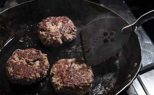 FILE-- Burgers are grilled in a pan in New York, June, 2018. On Sept. 30, 2019, in a remarkable turnabout, an international collaboration of researchers produced a series of analyses concluding that the advice to limit consumption of red meat and processed meats, a bedrock of almost all dietary guidelines, is not backed by good scientific evidence. (Karsten Moran/The New York Times)