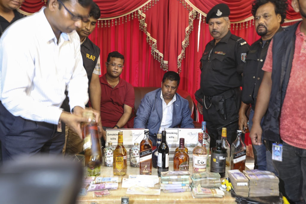 The Rapid Action Battalion seized a cache of local and foreign currencies worth over Tk 10.6 million and liquor in raids on the residence and office of Salim Prodhan, a man who allegedly operates online casino in Bangladesh, on Tuesday. Photo: Mahmud Zaman Ovi