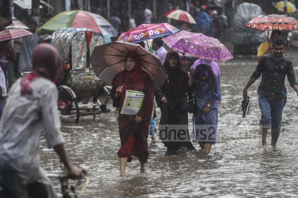 Pedestrians wading through water logged on Phoenix Road in Dhaka's Fulbaria after hours of rains on Tuesday. Photo: Abdullah Al Momin