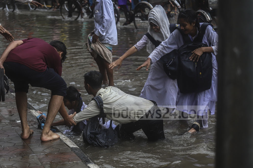Two college students fell in the waterlogged Phoenix Road after stepping into an uncovered drain at Fulbaria in Dhaka on Tuesday after hours of rains. Photo: Abdullah Al Momin