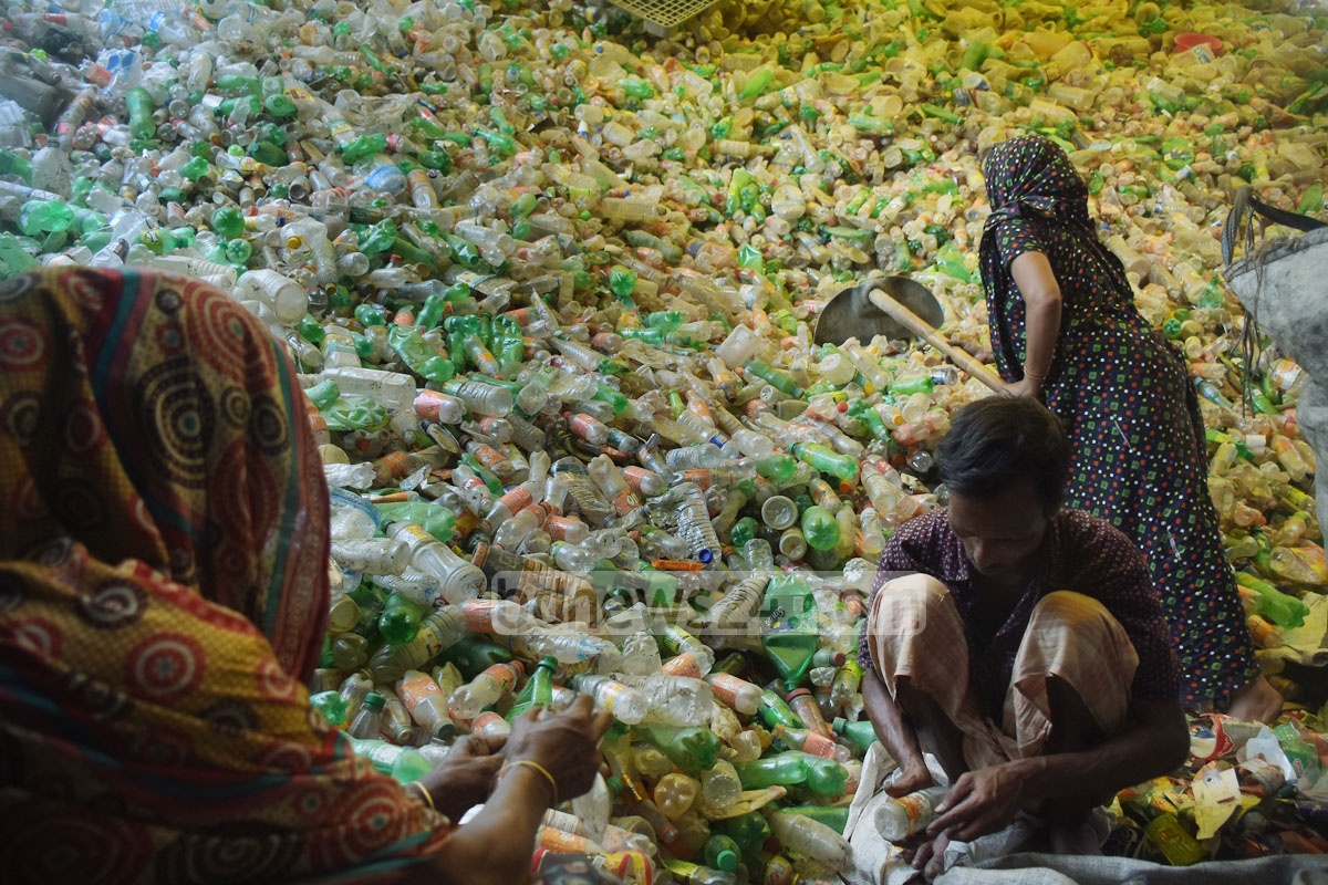 Workers collect plastic bottles from a scrapheap in Chattogram's Bakolia. The bottles are then taken to a recycling plant after which the plastic is exported to various countries, including India and China. Photo: Sumon Babu