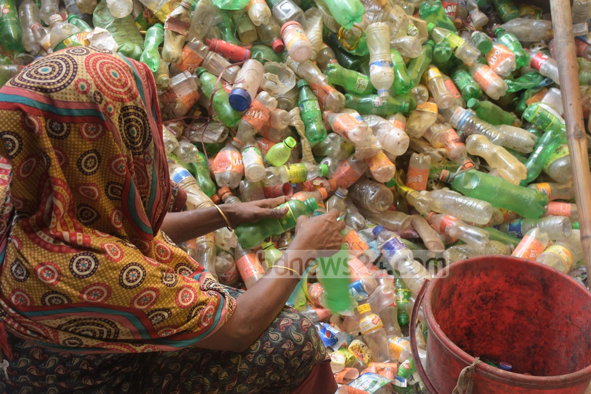 A woman collects plastic bottles from a scrapheap in Chattogram's Bakolia. The bottles are then taken to a recycling plant after which the plastic is exported to various countries, including India and China. Photo: Sumon Babu
