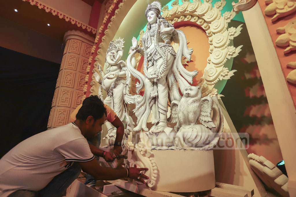 An artist giving the final touches to the idols at the Banani Puja Mandap in Dhaka on Thursday on the eve of the beginning of Durga Puja festival. Photo: Asif Mahmud Ove