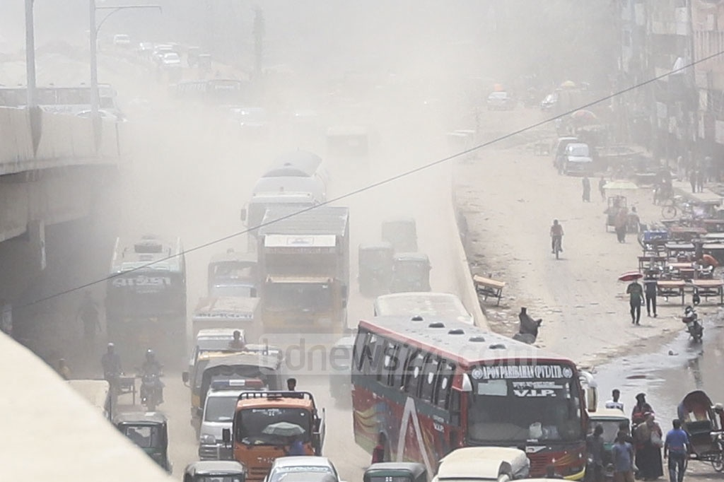 Mist-like dust covers the street in Dhaka's Jurain due to work on development of Dhaka-Mawa Road to a four-lane one.