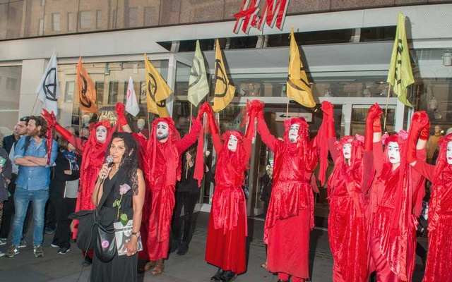 Extinction Rebellion protestors stage a mock funeral for fashion outside an H&M store during London Fashion Week, in London, Sep 17, 2019. The New York Times