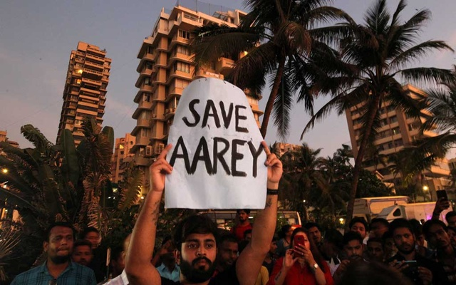 A man displays a placard at a promenade during a protest demanding that the Mumbai Metro Rail Corp Ltd (MMRCL) not cut trees to build a train parking shed for an upcoming subway line, in Mumbai, India, Oct 6, 2019. REUTERS