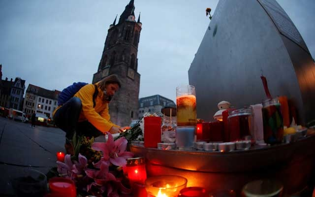 People place candles at central market square in Halle, Germany Oct 10, 2019, after two people were killed in a shooting. REUTERS