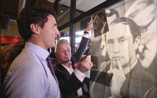 Liberal leader Justin Trudeau looks at a poster of his late father, former Prime Minister Pierre Trudeau, during a campaign stop at a coffee shop in Sainte-Therese, Quebec, October 15, 2015. Reuters