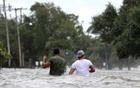 File Photo: People wade through a flooded street after Hurricane Barry in Mandeville, Louisiana, US Jul 13, 2019. REUTERS