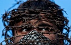 A masked Kashmiri man with his head covered with barbed wire attends a protest after Friday prayers during restrictions following the scrapping of the special constitutional status for Kashmir by the Indian government, in Srinagar, Oct 11, 2019. REUTERS
