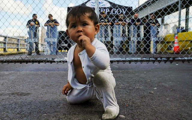 FILE PHOTO: A Mexican one-year-old baby, who is awaiting her turn to seek asylum in the US with her mother, is seen in front of the gates to the Gateway International Bridge in Matamoros, Mexico Oct 10, 2019. REUTERS