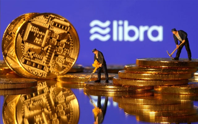 FILE PHOTO: Small toy figures are seen on representations of virtual currency in front of the Libra logo in this illustration picture, Jun 21, 2019. REUTERS