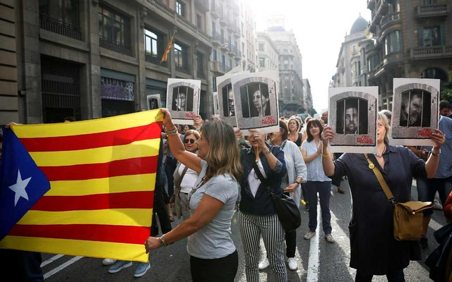 People holding an Estelada (Catalan separatist flag) and pictures of Catalan politicians as they walk through Via Laetana Avenue during a protest after a verdict in a trial over a banned independence referendum, in Barcelona, Spain October 14, 2019. REUTERS