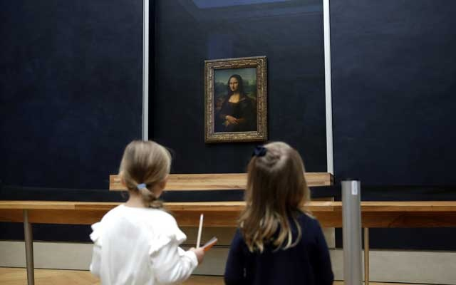 Two young girls look at the painting Mona Lisa (La Joconde) by Leonardo Da Vinci as it returns in the gallery where it is normally displayed, after works on the colour of the walls and a new glass screen, at the Louvre museum in Paris, France, October 7, 2019. Reuters