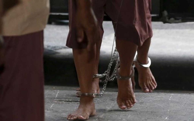 The shackled legs of suspected human traffickers are seen as they arrive for their trial at the criminal court in Bangkok, Thailand, Mar 15, 2016. REUTERS