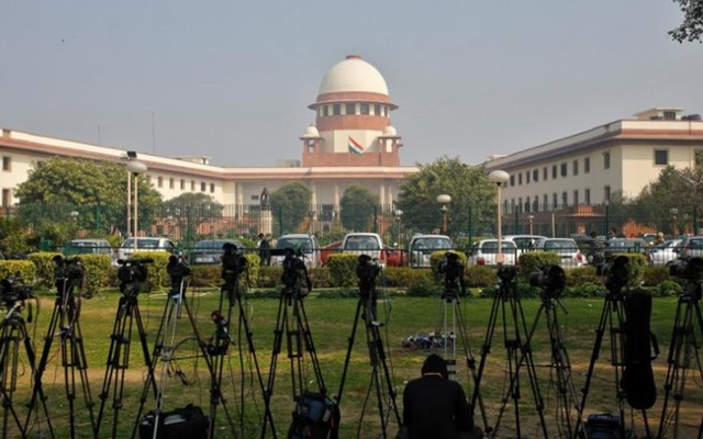 FILE PHOTO: A television journalist sets his camera inside the premises of the Supreme Court in New Delhi Feb 18, 2014. REUTERS